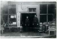 George Eliott with son Carl Curtis Elliott stand in doorway of Plumbing Shop