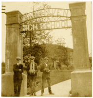 Three young men in ties and jackets stand under the arched gateway to Fairhaven High School, with the school in background
