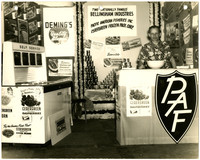 Man stands behind counter at promotional booth displaying products from Pacific American Fisheries and Cedergreen Frozen Pack Corp, including canned salmon and frozen raspberries