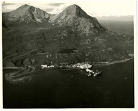 Aerial view of harbor with several cannery buildings and vessels moored, with moutains rising immediately in the background