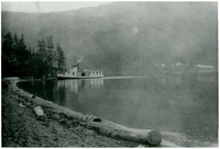 "Steamboat ""Marguerite"" pulls up to shore of Lake Whatcom, with forested hills in background"