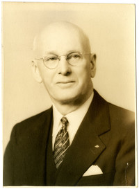 Studio portrait of unidentified older man in suit and spectacles