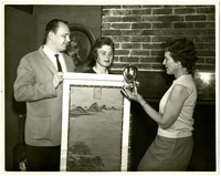 A man and two women display a piece of Asian art and a smlal ornamental object