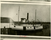 """A 72' wood-burining passenger and freight vessel named """"Islander"""" next to dock"""