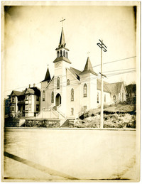 View from across street of front of Church of the Assumption, white with tall central spire and smaller spires in either side