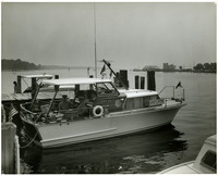 "Two uniformed men sit in 35' Owens Yacht  of the ""Safety Patrol, U.S. Coast Guard Auxiliary,"" moored at dock"