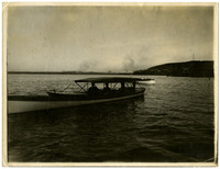 Small pleasure boat with two well-dressed men under the canopy