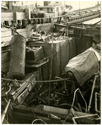 Deck of boat filled with clutter of machinery, furniture, other detritus, docked near other boats