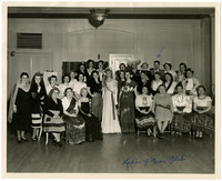 Group of twenty eight women, two men, pose seated and standing in large room, wearing traditional Mexican costumes