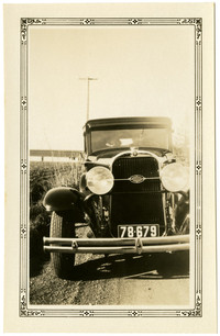 An early model car stopped next to field of row crop