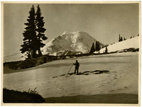 Hiker with hiking stick poses in snowfield with Mount Baker in background