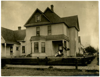 Exterior of 2.5-story house with children sitting on front corner porc