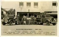 Men seated and standing in front of two fire engines parked in front of Blaine Fire Department