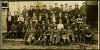 Forty five men pose in four rows outside warehouse or mill, all wearing work clothes