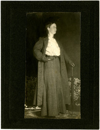 Woman poses in profile, modeling skirt and coat