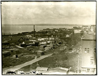 View of early settlement with lumber mill  and bay in distance, possibly Bellingham Bay