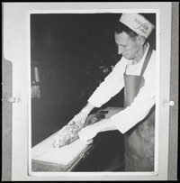 An unidentified man wearing a heavy apron and a Bornstein Seafoods hat and gloves, standing at a narrow table with a large fish laid out on it in front of him.