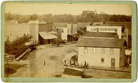 Pleasant Lake, Indiana. View from above of main street buildings, pedestrians, horse-drawn wagons, wide dirt streets of small town at turn of 20th century