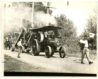 Large steam-powered tractor tows a large piece of equipment with several people atop and alongside