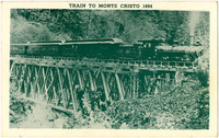 Steam locomotive pulls several passenger cars over trestle through forest en route to Monte Cristo, 1894