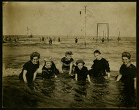 Six women in swimming costumes pose in shallow water, possibly in the ocean