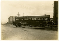 "A low, wooden building bearing sign ""Whatcom County Implement Co."" sits at intersection of unpaved roads"