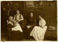 Several generations of women pose in parlor, with the eldest woman holding an infant