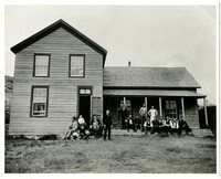 Several people and a dog, sitting and standing in front of L-shaped frame house