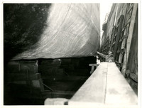 Unidentified man standing next to the hull of a ship that is in dry dock