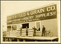 Three men stand by piles of feed sacks and a fourth man stans by a bike on the loading dock of Custer Feed & Grain Co.
