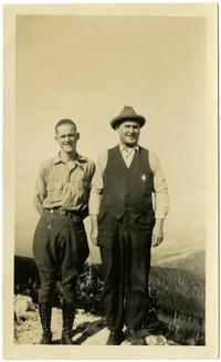 Two men, one wearing jhodpurs, pose on a mountainous bluff