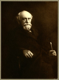 Studio portrait of unidentifiedelderly man seated, holding a cane or rod