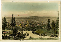 View from Sehome Hill of downtown Bellingham with early-model automobiles parked along Huntoon Drive leading down hill