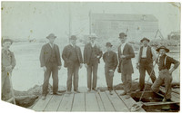 8 men, some in suits, some in work clothes, stand on plank sidewalk under construction