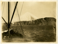 View from boat of snow-covered mountain with shoreline of cliffs