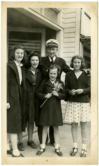 Four teenage girls pose with a man in a captain's uniform