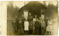 A teacher standing with twelve students of various ages in front of a simple, small wooden schoolhouse