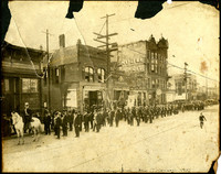 Men of unidentified fraternal organization and city officials stand in parade formation led by man on white horse on Holly Street, Bellingham, WA