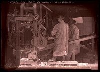 Three workers in wet gear operate the Smith Salmon Butchering Machine at cannery