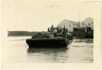 Naknet Cannery - Barge with men and materials is towed away from dock with cannery warehouses in background