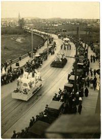 View from above of Cornwall Avenue's raised section, lined with early-model cars and people watching several parade floats pass
