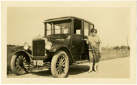 Woman posing next to automobile on roadside