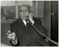 Unidentified, but likely George D. Zahn, Chairman of the Washington State Highways Commission, sitting at a desk, with the telephone receiver to his ear, a lighted cigar in his other hand