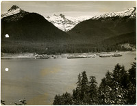 View from hillside of bay or inlet with several docks and buildings on opposite shore, snowy mountain peaks in background