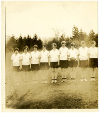 Soccer Girls - nine teenage girls pose in athletic uniforms with a ball on a playing field