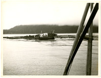 An unidentified ship listing on its side, marooned on rocks.