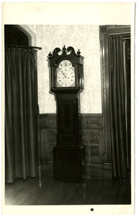 A Chippendale grandfather clock stands against a wall with ornate wainscotting