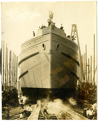 """Newly built ship """"Blythedale"""" in shipyard, being launched with men and American flags at its prow"""
