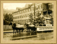 """Four-horse-drawn """"Junior Order United American Mechanics"""" parade float adorned with evergreen trees, American flags, sitting platform"""