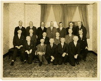 Eighteen men in suits pose in three rows in wallpapered room